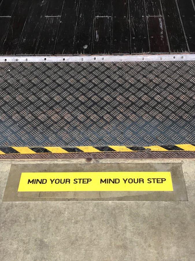 Żółty i czarny znak ostrzegawczy na kroka twierdzić obrazy stock