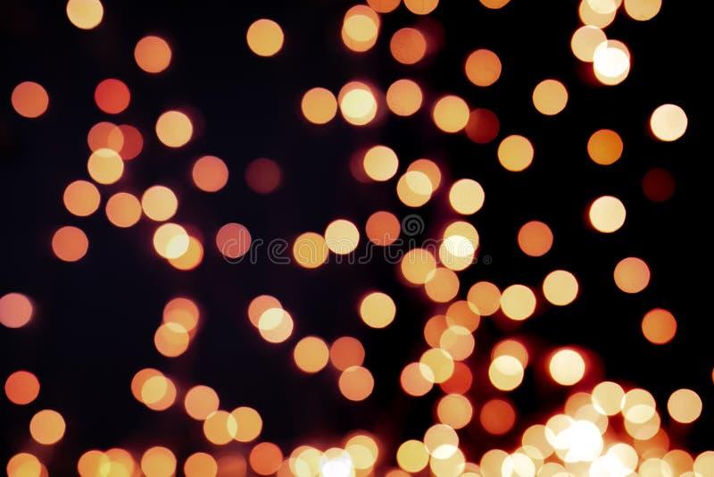 Żółty i pomarańczowy choinki bokeh na czarnym tle defocused połyskuje światła, Bożenarodzeniowy tło wzoru pojęcie zdjęcia royalty free
