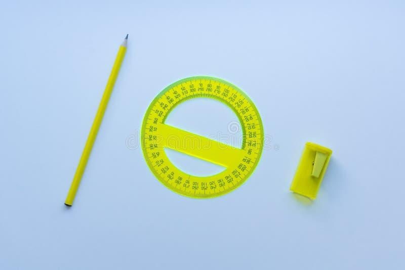 Żółty materiały ustawiający: ołówek, kątomierz, ostrzarka od odgórnego widoku na białym tle fotografia stock