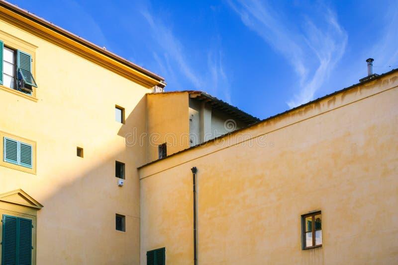 żółty mieszkanie dom pod niebieskim niebem w Florencja fotografia royalty free