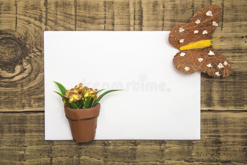 Żółty motyl i kwiaty z białą księgą, copyspace na drewnianym tle pojęcie lato, kartka z pozdrowieniami, sztandar, ulotka obraz stock