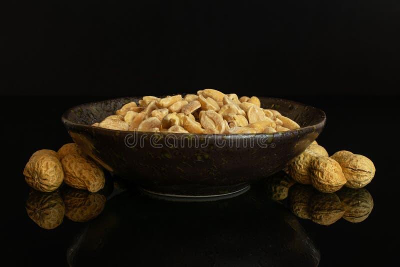 Żółty naturalny arachid odizolowywający na czarnym szkle zdjęcie stock