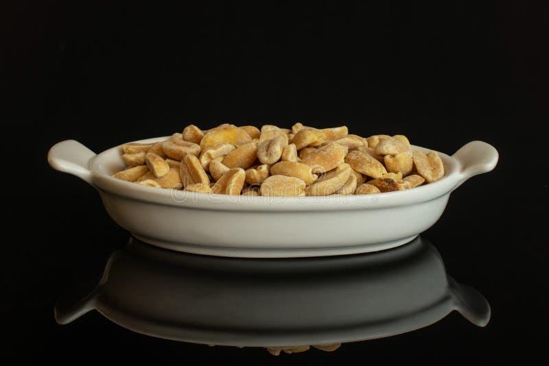 Żółty naturalny arachid odizolowywający na czarnym szkle zdjęcie royalty free