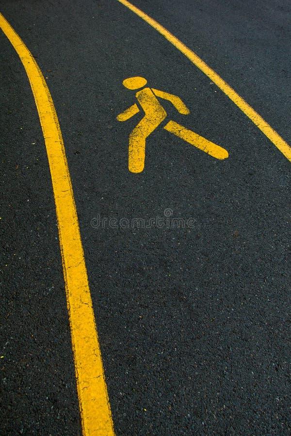 Żółty odprowadzenie śladu symbol na czarnej asfaltowej drodze obrazy royalty free