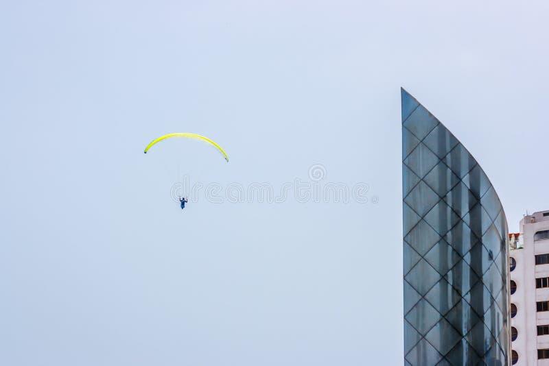 Żółty paraglider obok drapacza chmur nad Lima, Peru obrazy stock
