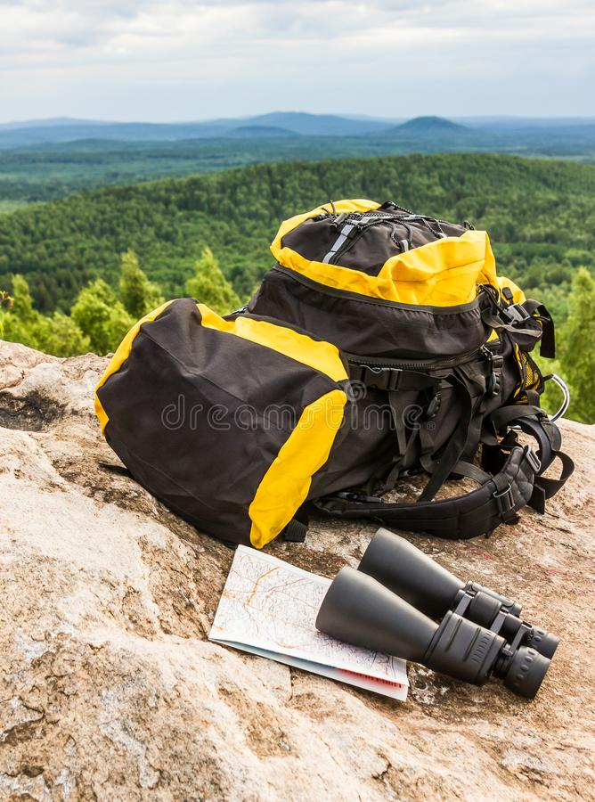 Żółty plecak z turystycznym wyposażenie lornetek mapy podróży turystyki widokiem zdjęcia royalty free