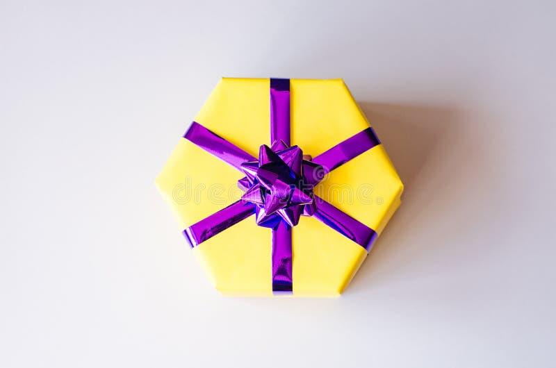 Żółty prezenta pudełko z purpurowym łękiem obraz stock