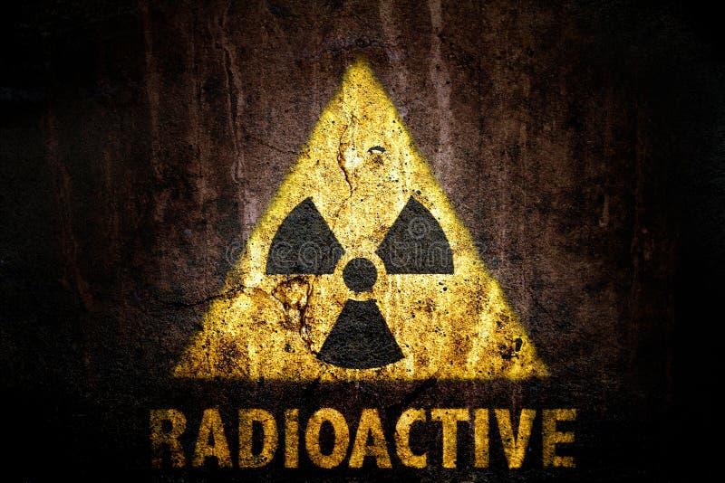 Żółty promieniotwórczy jonizacyjnego napromieniania niebezpieczeństwa symbol z słowa promieniotwórczym malującym pod znakiem zdjęcie royalty free