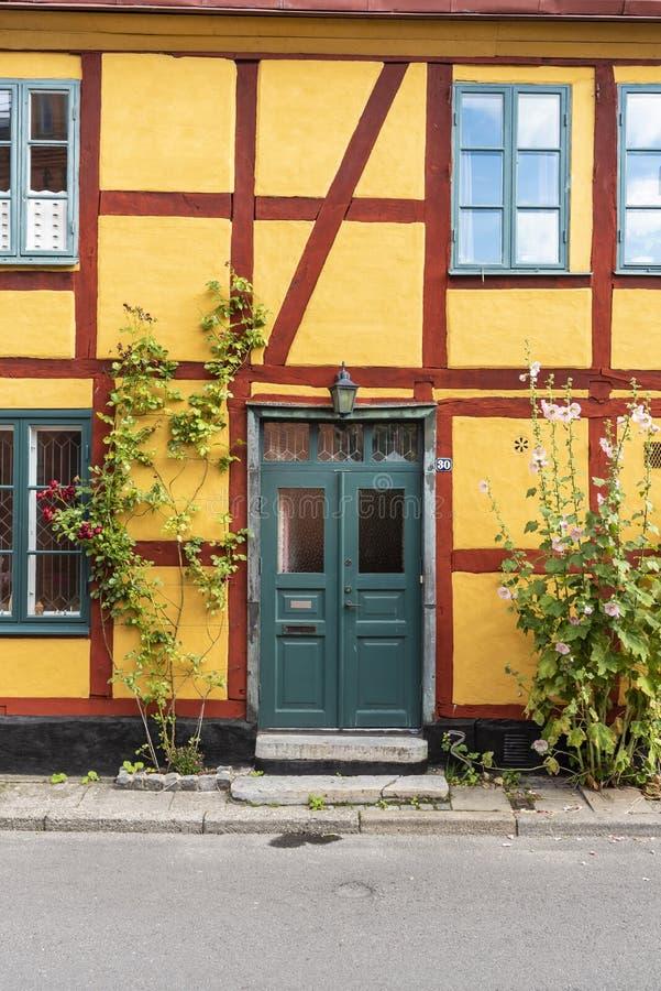 Żółty ryglowy dom z zielonym ulicznym drzwi Ystad fotografia royalty free