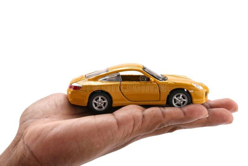 Żółty samochód w mężczyzna ` s rękach na białym tle zdjęcie stock