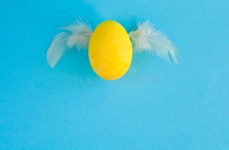 Żółty Wielkanocny jajko z skrzydłami na błękitnym tle z kopii przestrzenią fotografia stock