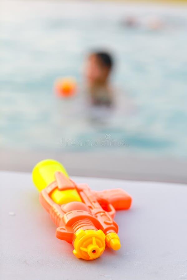 Żółty wodny pistolet pływackim basenem, wakacje letni pojęcie obrazy royalty free