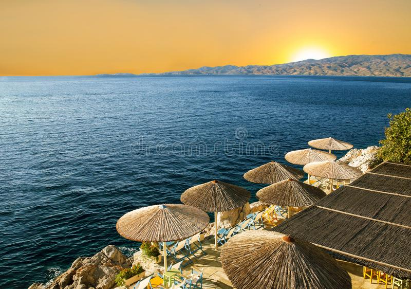 Żółty wschód słońca W Grecja Krzesła i pokrywać strzechą markizy obrazy royalty free