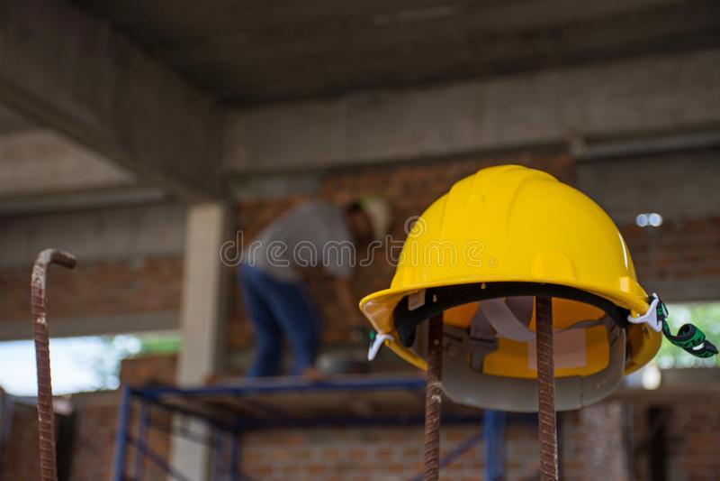 Żółty zbawczy hełm z pracownikiem budowlanym umieszcza cegły dalej zdjęcia stock