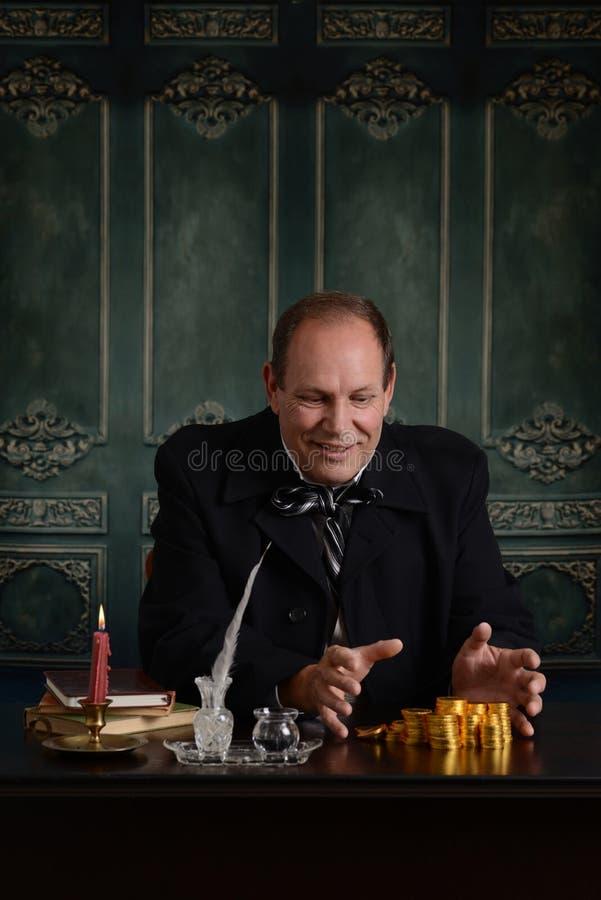 Żądny wiktoriański harpagon szczęśliwy z stosem pieniądze zdjęcie stock