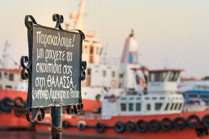Żadny Śmiecić signboard pisać w grku Zadawala śmieci, no rzuca morze umieszczający przy nabrzeżem Rhodes, Grecja obraz stock