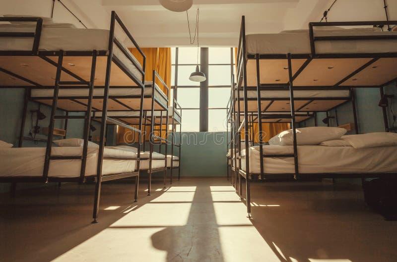 Żadny ludzie inside schronisko sypialni z czystymi białymi koj łóżkami dla uczni i turystów zdjęcie stock