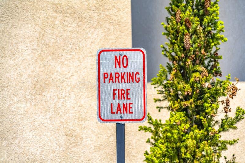 Żadny parking Pożarniczego pas ruchu znak z ścianą w tle i drzewem zdjęcia royalty free