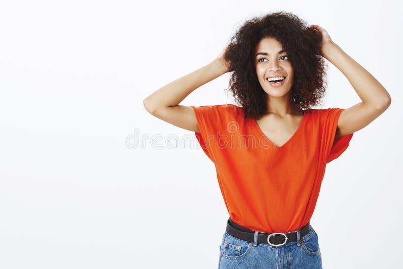 Żadny zmartwienia, dziewczyny czuć beztroski Atrakcyjny życzliwy żeński uczeń z afro fryzurą, podnoszący ręki i macanie obrazy royalty free
