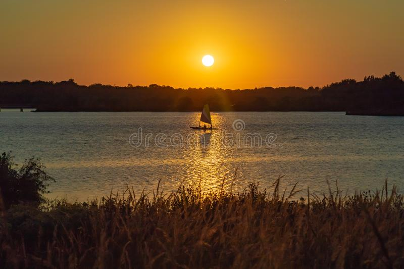 Żagiel łodzi cień z Jasnym konturem słońce przy zmierzchem z piękną linią horyzontu nad jeziornym Zorinsky Omaha Nebraska obraz stock