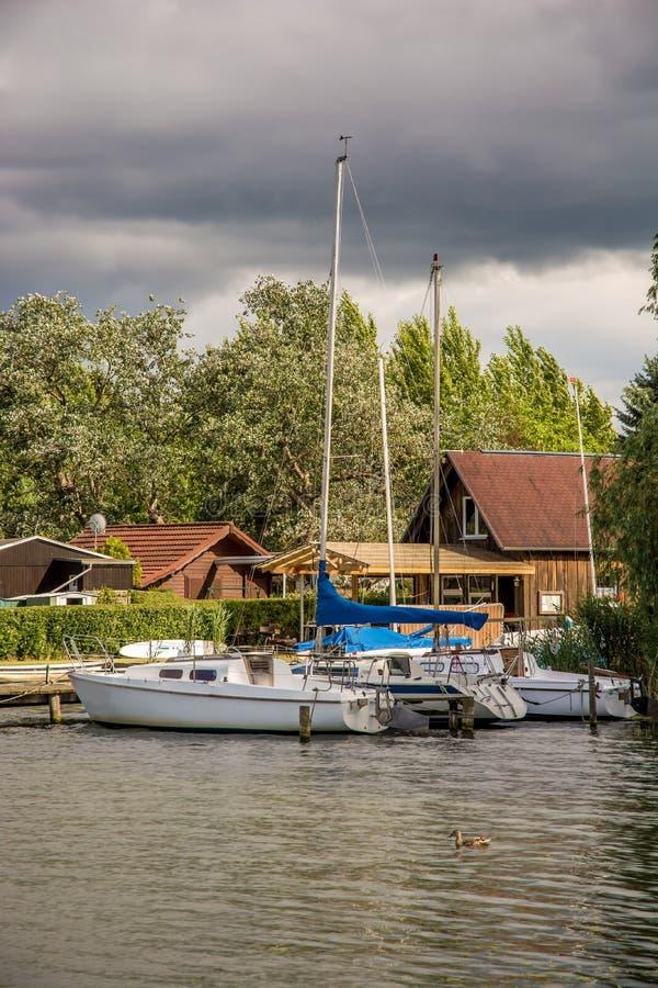 Żaglówki kłamają na jetty z pięknym drewnianym domem w tle fotografia royalty free