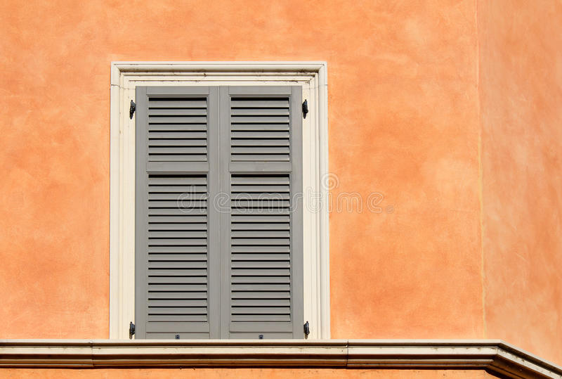 Żaluzi okno na pomarańczowej ścianie obrazy royalty free