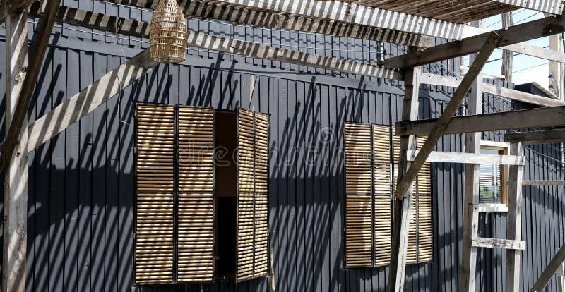 Żaluzje, cienie i cienie na czarnej fasadzie, zdjęcie royalty free