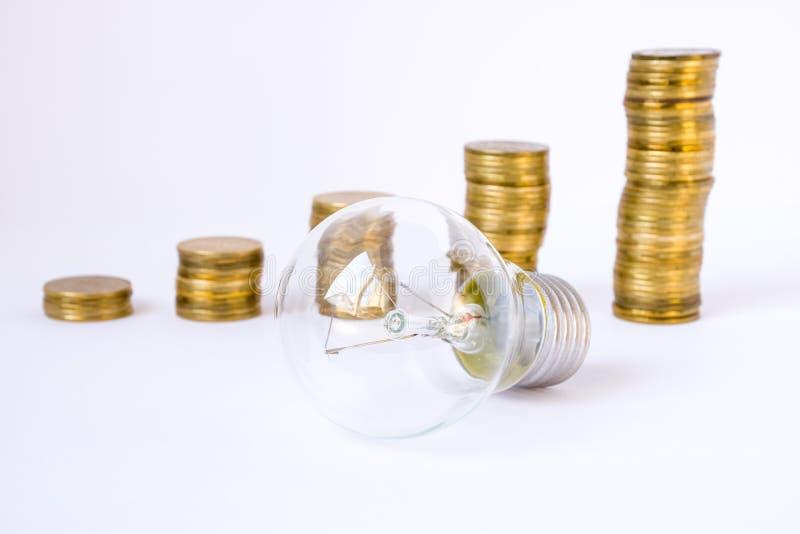 Żarówka jest na tle sterty lub kolumnach monety w wstępującym rozkazie Pojęcie fotografia ratuje elektryczną energię ludźmi i zdjęcia royalty free