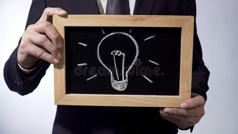 Żarówka rysunek na blackboard, samiec w czarnym kostiumu mienia znaku, biznesowy pomysł obraz royalty free