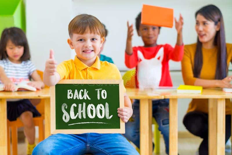 Żartuje chłopiec aprobaty i mienia blackboard z z powrotem szkoły wor obrazy royalty free