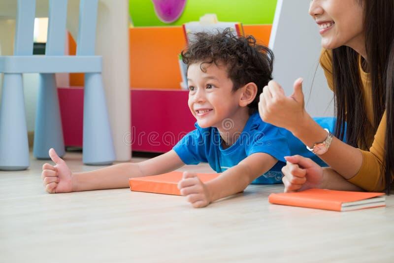 Żartuje chłopiec aprobaty z nauczycielem podczas gdy łgarski puszek na sala lekcyjnej flo fotografia royalty free
