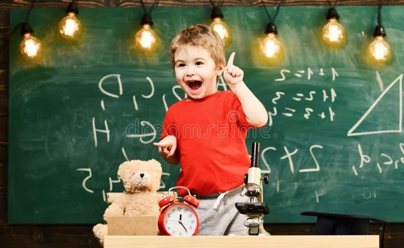Żartuje chłopiec blisko mikroskopu w sala lekcyjnej, chalkboard na tle Pierwszy poprzedni z podnieceniem o studiowaniu, uczenie,  obrazy royalty free