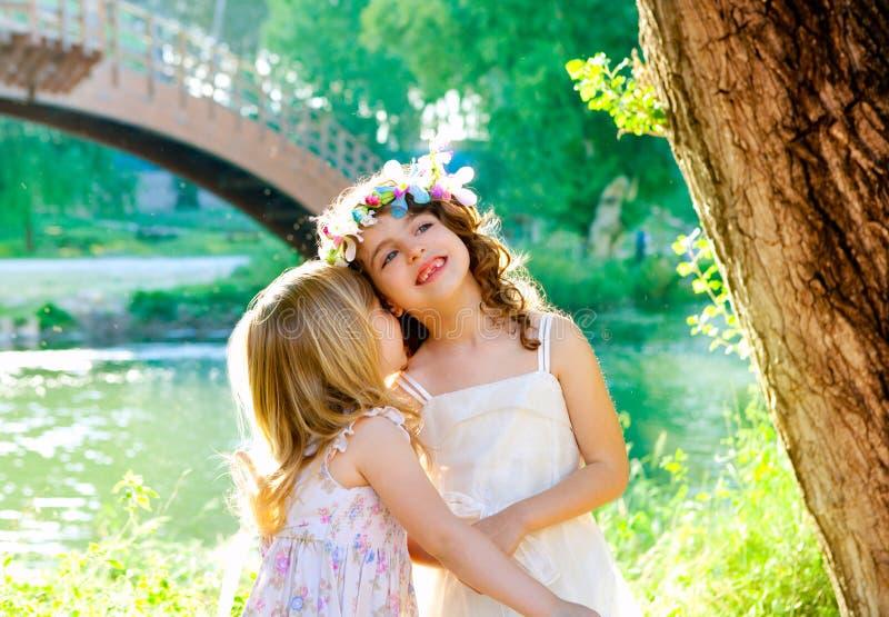 Żartuje dziewczyny bawić się w wiosna plenerowym rzeki parku zdjęcia stock