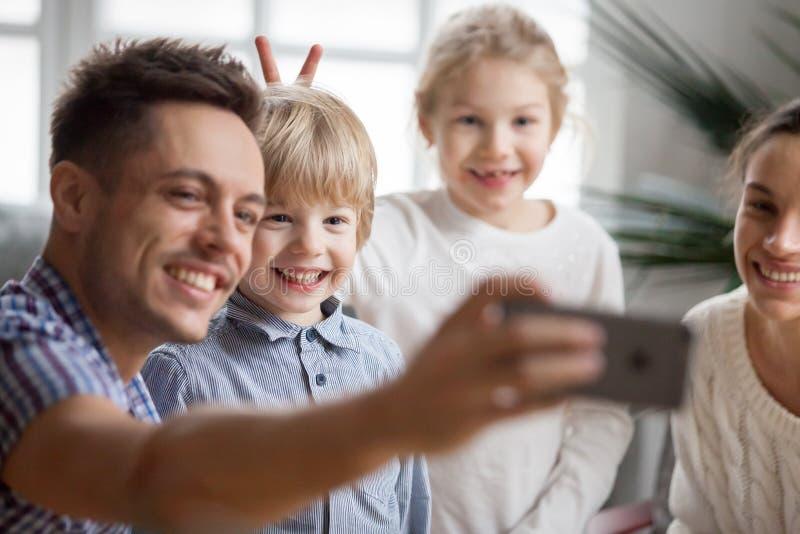 Żartuje dziewczyny robi brata królika ucho podczas gdy ojciec bierze selfie obrazy stock