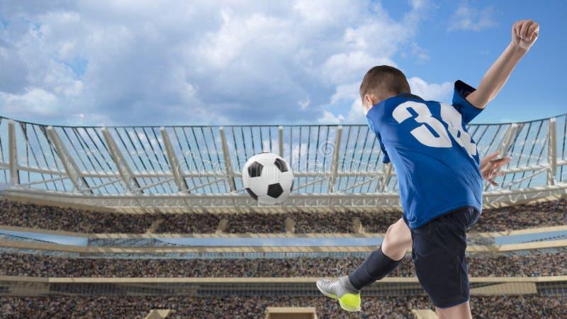 Żartuje gracza futbolu uderza piłkę na stadium piłkarski fotografia stock