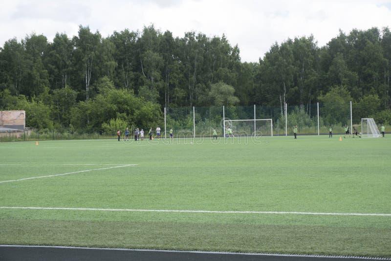 Żartuje piłek nożnych młodych dzieci futbolowych graczów dopasowanie na boisku piłkarskim, Rosja Berezniki 25 2017 Jul zdjęcia stock
