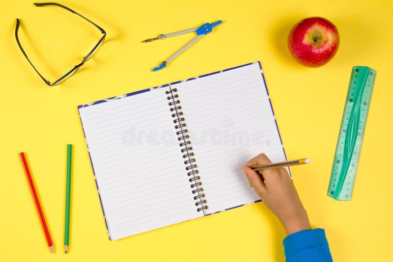 Żartuje rękę z otwartym notatnikiem, piórem, władcą, szkłami i świeżym jabłkiem na żółtym tle, obrazy royalty free