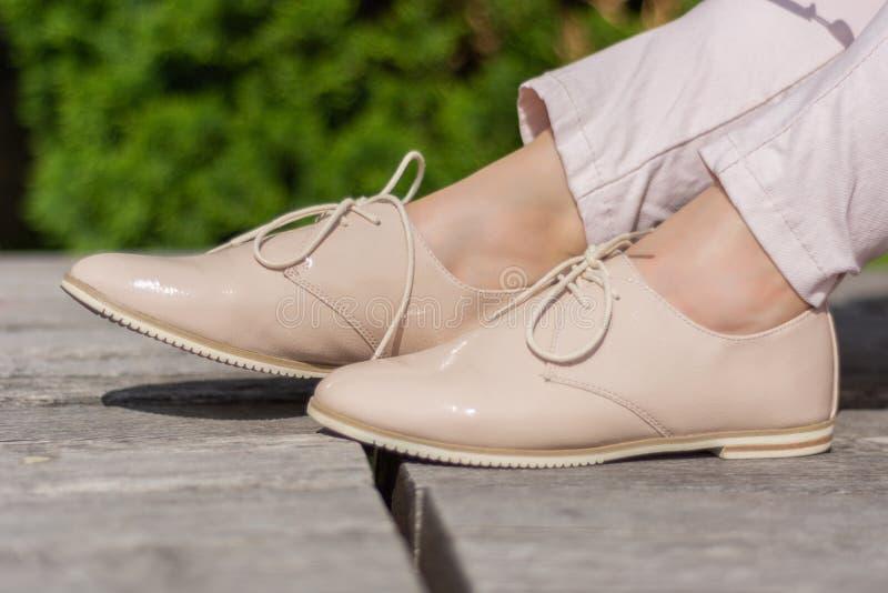 Żeńscy beżowi kolor laki buty na ławki i dziewczyny odzieży menchii spodniach, naga skóra wokoło nogi kostki obrazy stock
