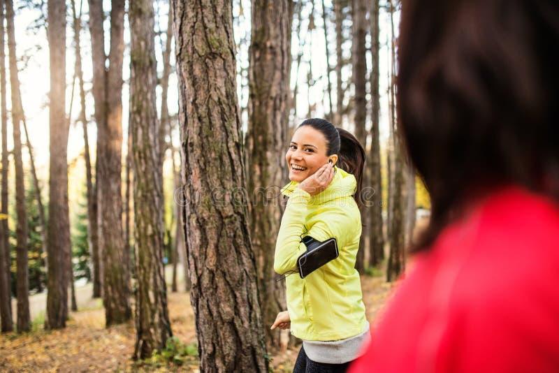 Żeńscy biegacze z słuchawkami i smartphones jogging outdoors w lesie obrazy royalty free