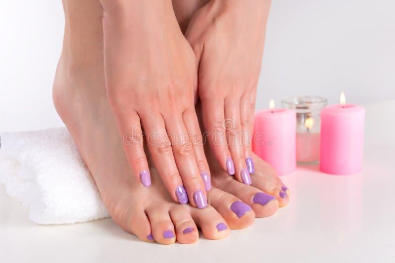 Żeńscy cieki i ręki z lilym gwoździa połyskiem barwią zdjęcie stock