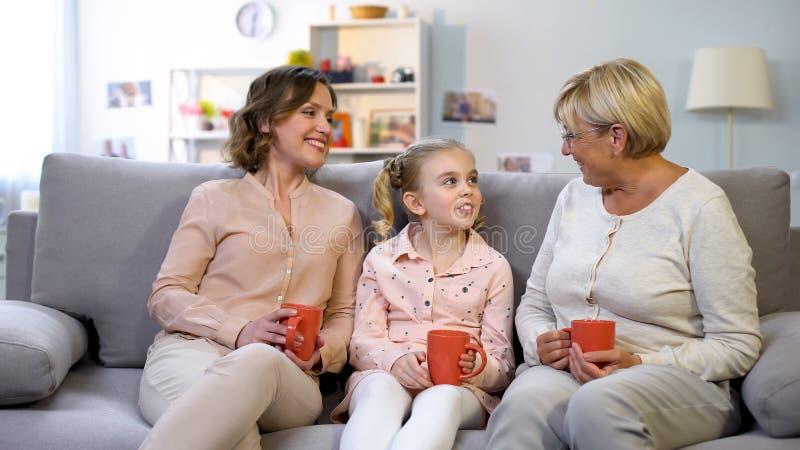 Żeńscy członkowie rodzini opowiada siedzieć na domowej kanapie z filiżankami herbata, pokolenie zdjęcia stock