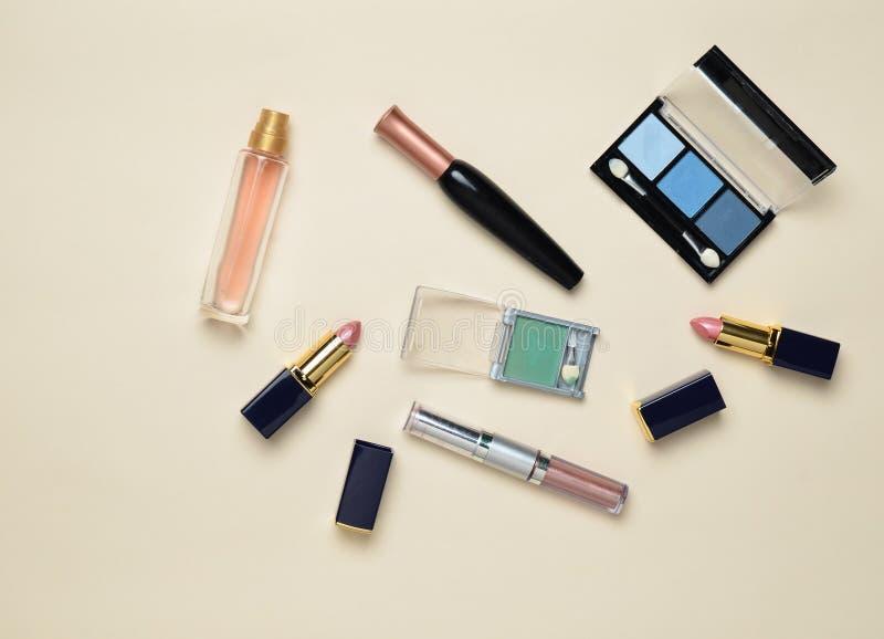 Żeńscy kosmetyki dla makijażu układu na pastelowym tle Kosmetyk ocienia, makijażu muśnięcie, eyeshadow pomadka, pachnidło butelka obrazy royalty free