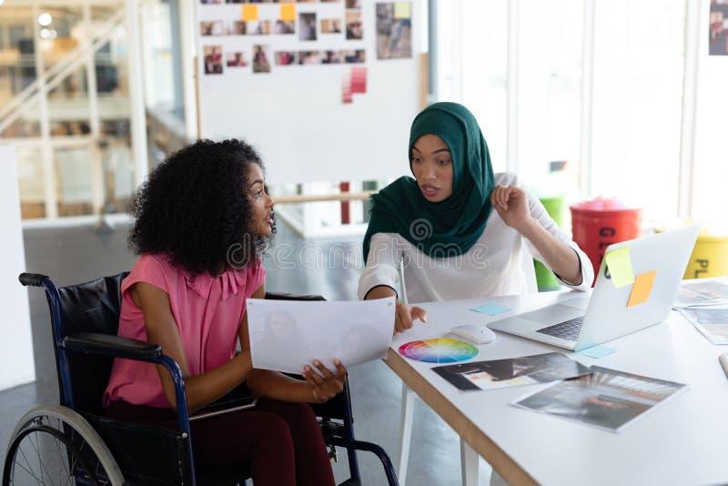 Żeńscy projektant grafik komputerowych dyskutuje nad fotografiami przy biurkiem zdjęcia royalty free