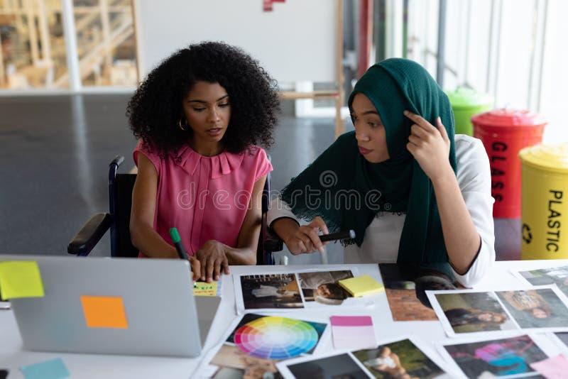 Żeńscy projektant grafik komputerowych pracuje wpólnie przy biurkiem zdjęcie royalty free