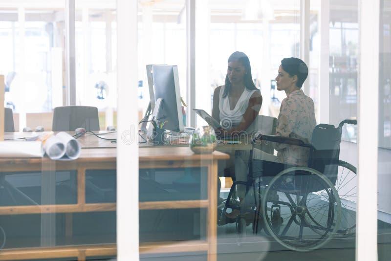 Żeńscy projektant grafik komputerowych pracuje wpólnie przy biurkiem w nowożytnym biurze fotografia stock