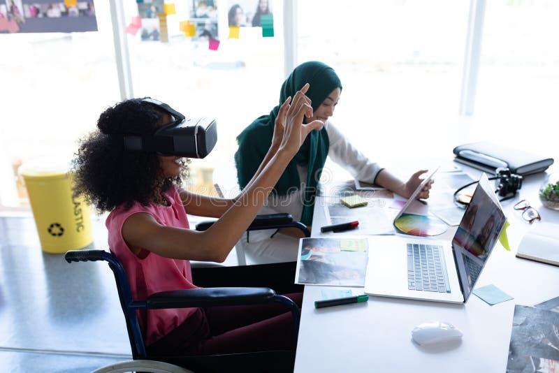 Żeńscy projektant grafik komputerowych używa rzeczywistości wirtualnej słuchawki i cyfrową pastylkę przy biurkiem fotografia stock