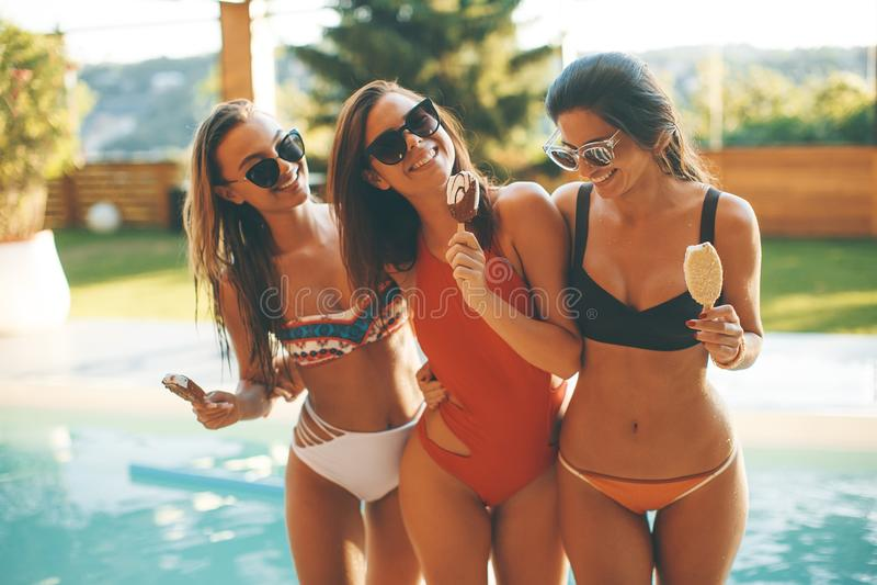 Żeńscy przyjaciele je lody basenem w lecie zdjęcie stock