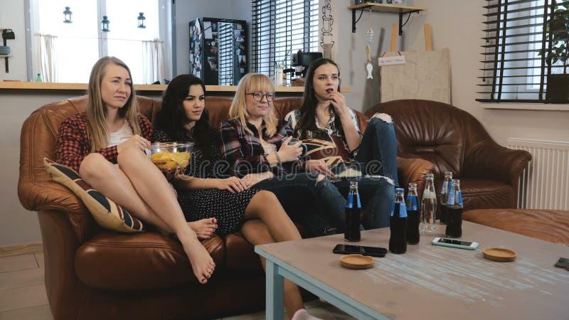 Żeńscy przyjaciele oglądają smutnego film na TV w domu Młode piękne Europejskie dziewczyny ogląda romantyczną emocję filmują kome zdjęcia royalty free