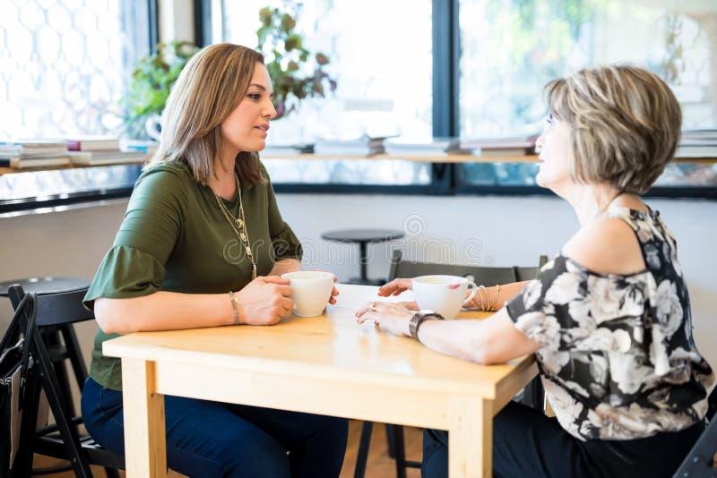 Żeńscy przyjaciele spotyka przy kawiarnią zdjęcie royalty free