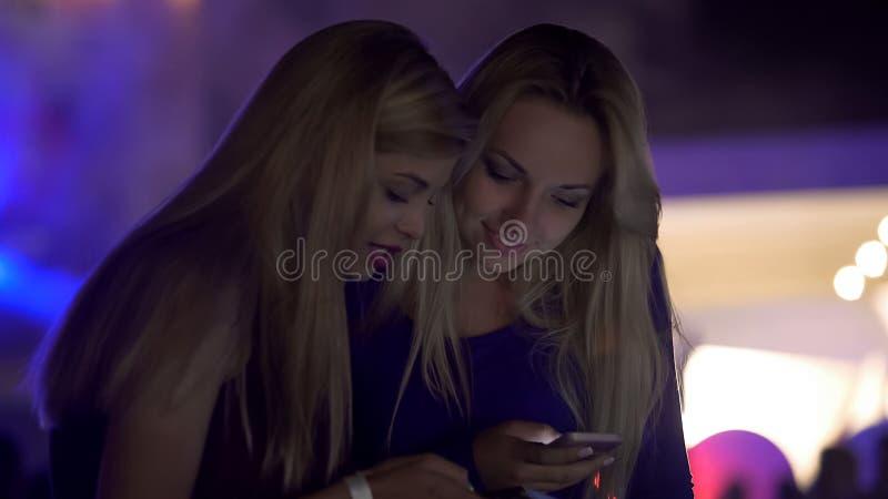 Żeńscy przyjaciele używa smartphones przy przyjęciem, gawędzi online z uśmiechami na twarzach zdjęcia royalty free